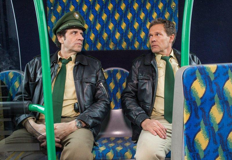 Hubert (Christian Tramitz, rechts) und Staller (Helmfried von Lüttichau) müssen mit dem Bus zum Revier fahren, da sie vergessen haben zu tanken und mit ihrem Polizeiauto liegen geblieben sind. Sie streiten sich, wer Schuld am leeren Tank hat. – Bild: BR/ARD/TMG/Arvid Uhlig