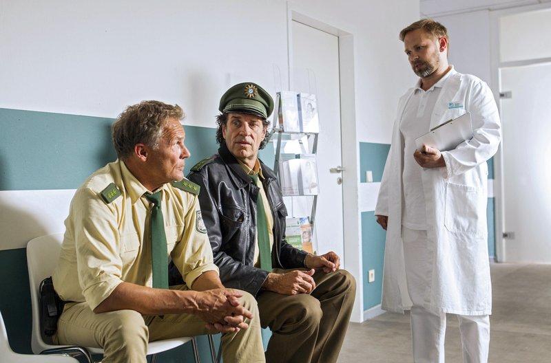 Der Arzt eröffnet Staller (Helmfried von Lüttichau, 2.v.l. mit Christian Tramitz, l.), dass er ab jetzt gesund leben muss. – Bild: ARD/TMG/Chris Hirschhäuser
