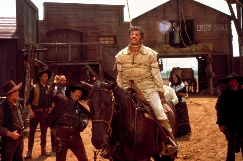 Höhepunkt ihres Cowboy-Spektakels: Tuco (Eli Wallach, M.) hat die Schlinge um den Hals, und Freund Joe (Clint Eastwood, rechts oben) zerschießt mit seinem Gewehr den Strick. – Bild: ZDF und Angelo Novi