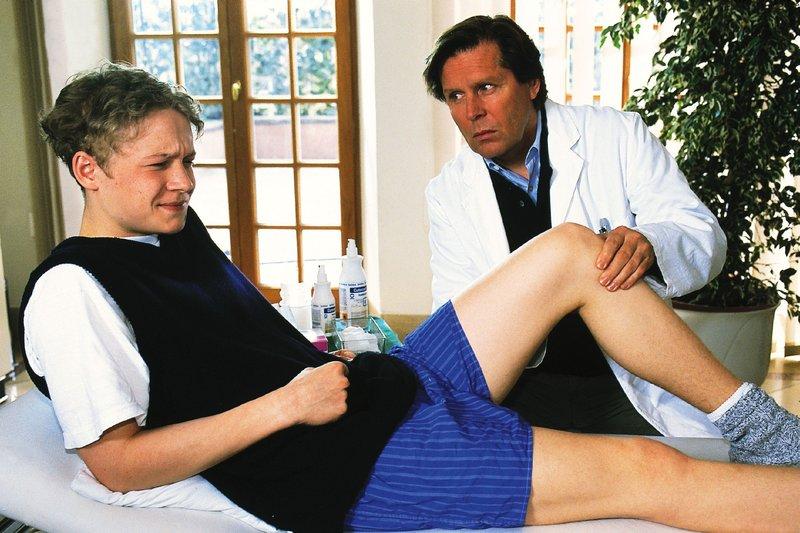 Dr. Stefan Frank (Sigmar Solbach, re.) untersucht Ingos (Matthias Schweighöfer) Knie. Seine Diagnose ist niederschmetternd: In Ingos Knie hat sich ein lebensgefährlicher Tumor gebildet... – Bild: RTLplus