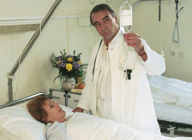 Eva (Sylvia Haider) liegt wegen einer Schußverletzung im Krankenhaus und ist bei Dr. Wohlmann (Walter Kreye) in Behandlung. Sie hat das seltsame Gefühl, dass mit diesem Arzt irgendetwas nicht stimmt... – Bild: RTLplus