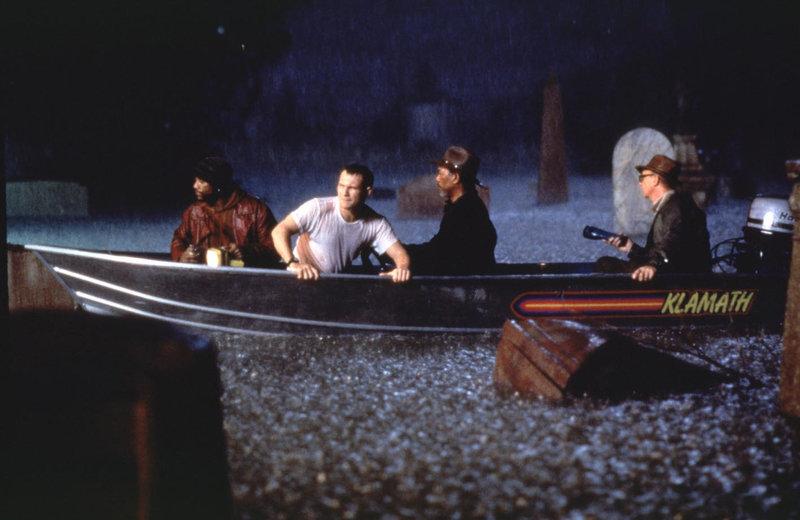 In der überfluteten menschenleeren Stadt wird Geldtransportfahrer Tom (Christian Slater) von Gangster Jim (Morgan Freeman) und dessen Komplizen Ray (Ricky Harris) gefangen genommen, da er den Bargeldbestand des Orte in Sicherheit gebracht hat. – Bild: TMG