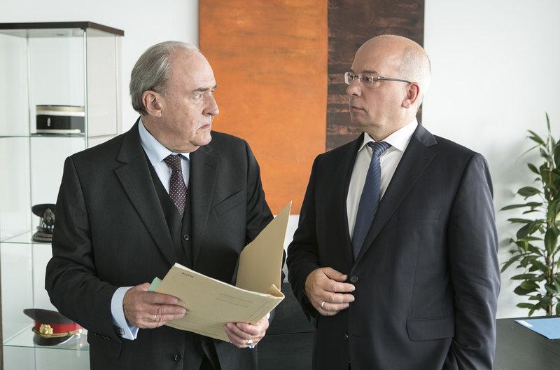 Plocher (Michael Prelle, l.) hat den Bundesvorsitzenden der deutschen Polizeigewerkschaft, Rainer Wendt (Rainer Wendt, r.), zu Gast, der sich über die Arbeitsbedingungen der beiden reaktivierten Rentner informieren will. – Bild: ARD/Kai Schulz