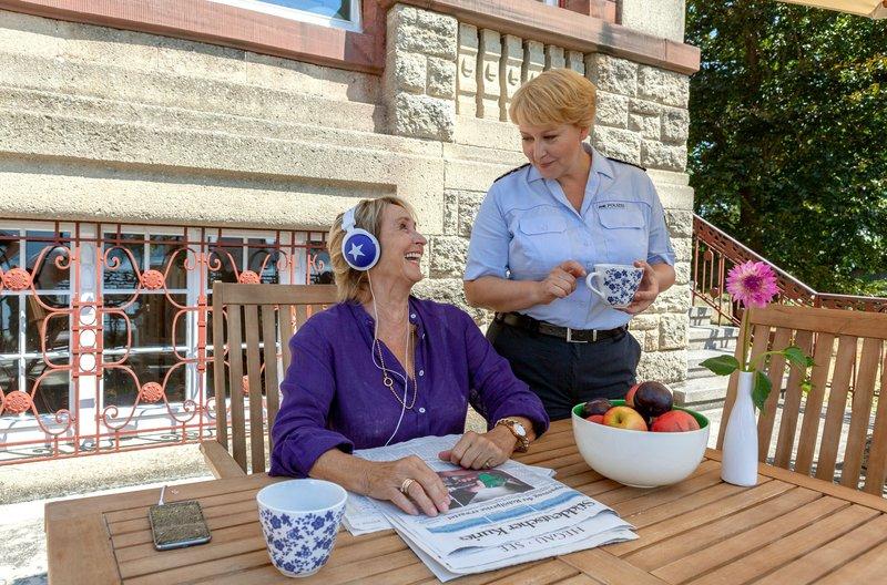 Nele Fehrenbach (Floriane Daniel, r.) amüsiert sich über ihre Mutter Mechthild (Diana Körner, l.): Weil sie das Hundegebell aus dem Nachbargarten nicht ertragen kann, hört sie mit den Kopfhörern von Niklas klassische Musik. – Bild: Das Erste