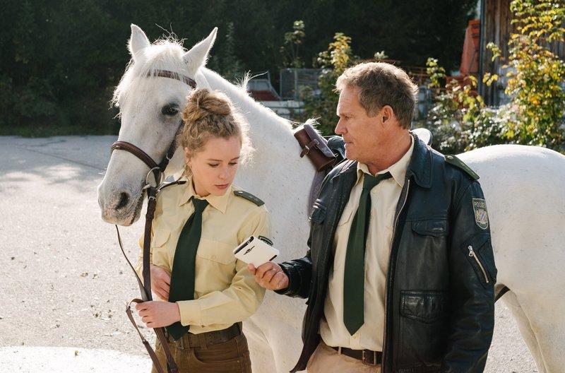 Das herrenlose Pferd mit dem Handy in der Satteltasche gibt Hubert (Christian Tramitz, r.) und Lena (Klara Deutschmann, l.) Rätsel auf. – Bild: ARD/BR/TMG/Emanuel Klempa