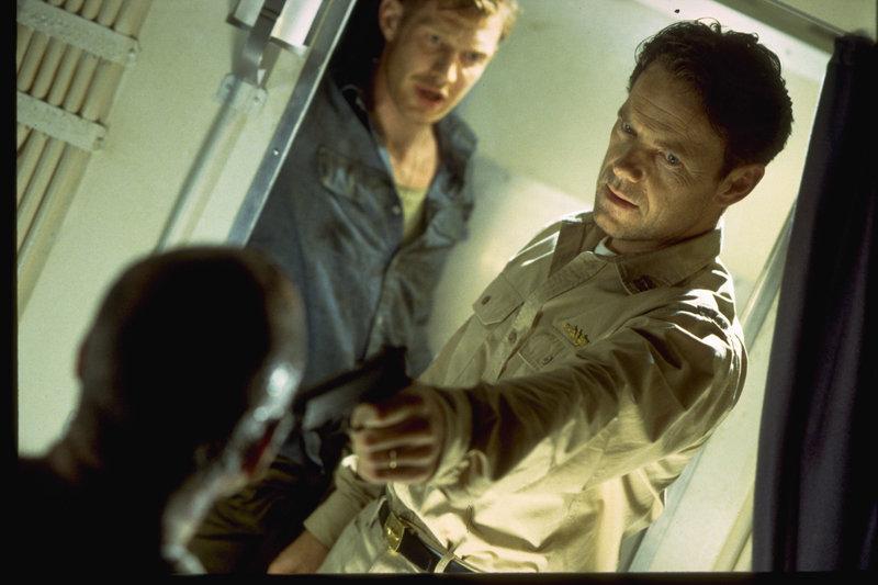 Lieutenant Commander Brice (Bruce Greenwood, r.) kommt hinter Bernhard Schillings (Jonathan Hartman, l.) Geheimnis und macht ihn für die mysteriösen Vorfälle verantwortlich. Brice ist entschlossen jeden zu bekämpfen, der seine Crew in Gefahr bringt. Auch Stumbo (Jason Flemyng, M.) kann ihn nicht davon abhalten. – Bild: ZDF und Miramax