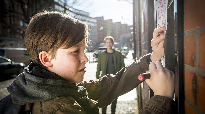 Johannes (Luke Matt Röntgen) beobachtet, wie ein mysteriöser Junge (Nikita Lysko, vorn) vorm CafĂ – Bild: NDR/Boris Laewen