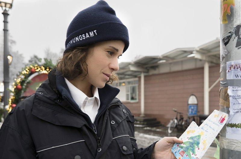 Pauline (Anne Schäfer) findet den handgeschriebenen Wunschzettel eines kleinen Jungen. – Bild: ARD Degeto/Christian Lüdeke