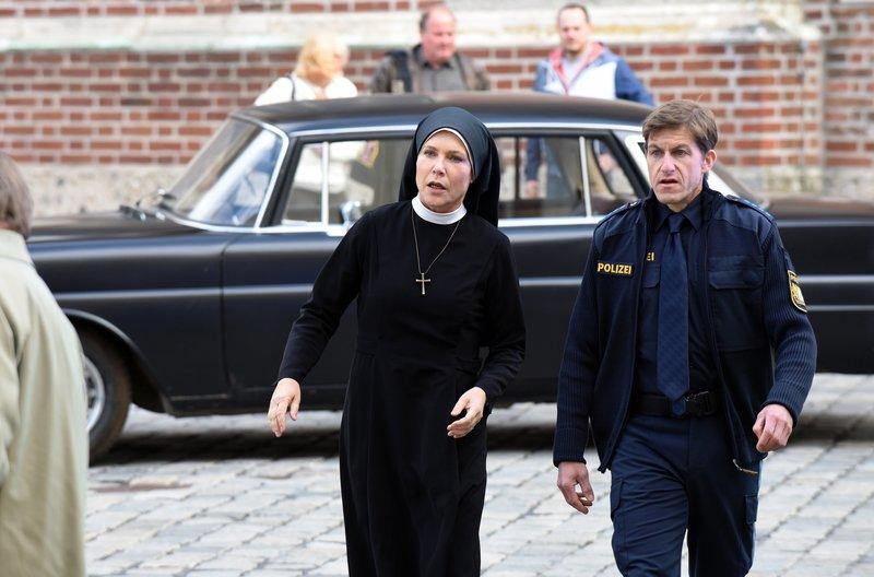 Schwester Hanna (Janina Hartwig, l.) und Polizist Meier (Lars Weström, r.) eilen zur Bushaltestelle. Angeblich ist ein Halbbruder von Wöller angekommen. – Bild: ARD/Barbara Bauriedl