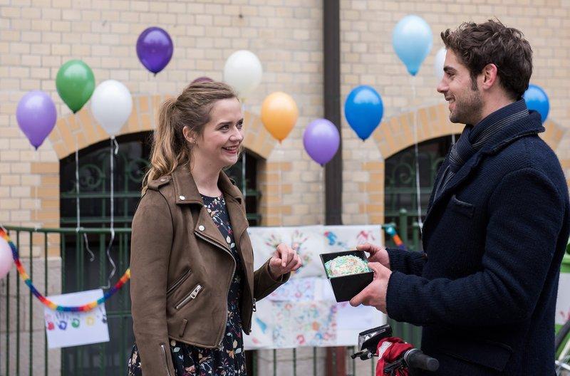 Niklas (Roy Peter Link, r.) bringt Eva (Sarina Radomski, l.) einen Kuchen zum Fest. – Bild: ARD/Jens Ulrich Koch