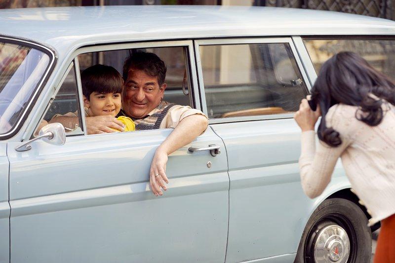 Rückblende (1977): Der achtjährige Semir (Ilia Djahed) posiert mit seinem Vater Abdulkabir (Hasan Ali Mete) vor dem Teppichladen der Familie für ein Foto, das seine Mutter Selma (Pina Ernicin) macht. – Bild: TVNOW / Guido Engels