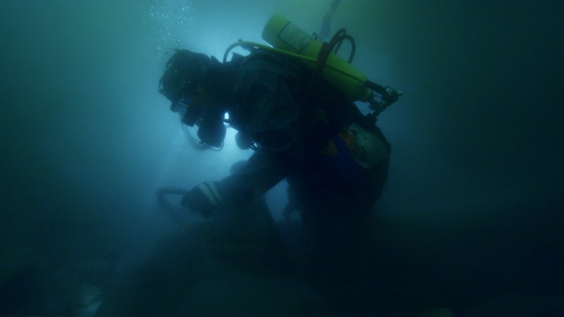 Juston Cook dredging underwater with light in background. – Bild: Discovery Communications