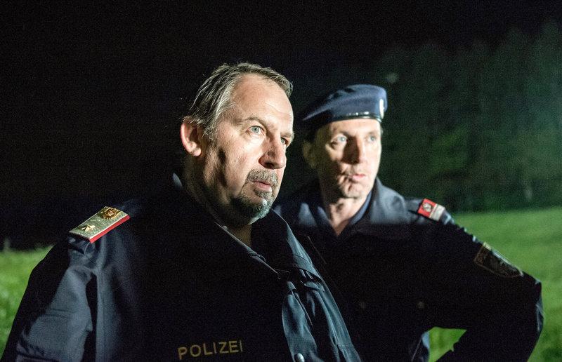 Felix Hörtnagel (Wolf Bachofner, l.), Polizeichef von Mairach, wünscht die SOKO Kitzbühel zum Teufel, die sich in die inneren Angelegenheiten seines Reviers einmischt, um einen Mord aufzuklären. Sein Mitarbeiter Josef Schratt (Rainer Egger, r.) ist auf seiner Seite. – Bild: ORF