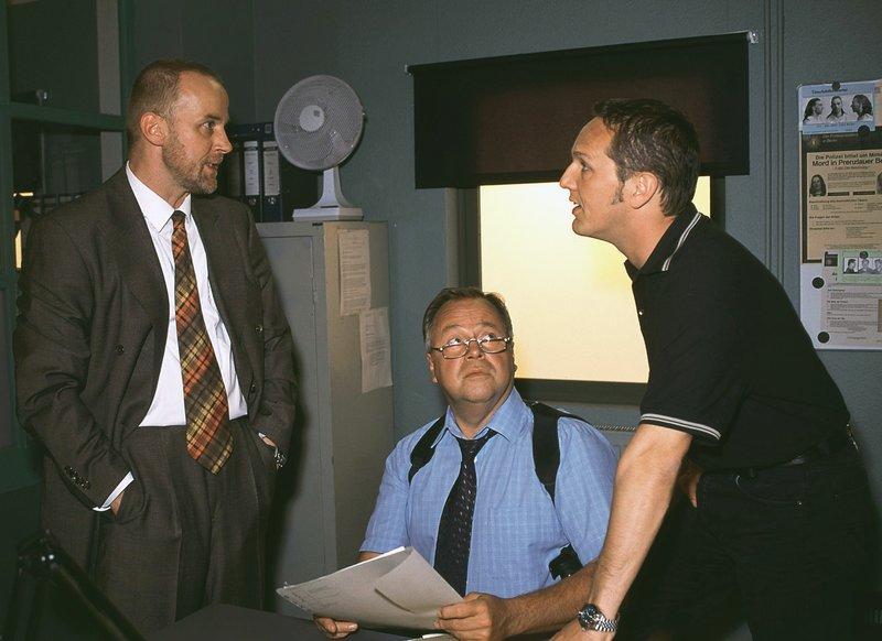 Jürgen Branner (Conrad F. Geier, li.) wird von Kriminalhauptkommissar Stefan Kehler (Wolfgang Bathke, Mi.) und Kriminalkommissar Bongartz (Max Gertsch) vernommen. – Bild: RTLplus