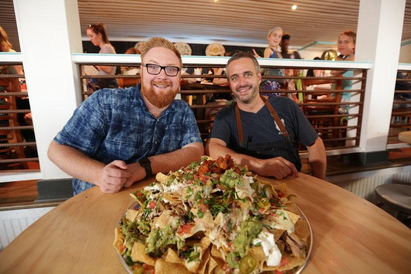 """Im """"Mex 1 Coastal Cantina"""" in Charleston stattet Josh (l.) Koch Ryan Jones (r.) einen Besuch ab und probiert seine beliebten """"Big Pappa Nachos"""" ... – Bild: 2017,Television Food Network, G.P. All Rights Reserved. Lizenzbild frei"""