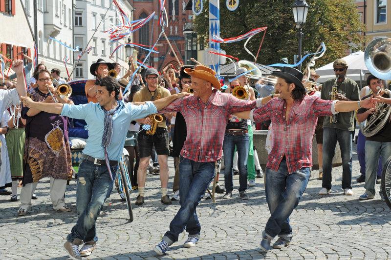 Sirtaki tanzende Cowboys in München: Nektarios (Adam Bousdoukos, r.) mit Ehemann Lambert (Heiner Lauterbach, m). – Bild: ZDF und Kerstin Stelter
