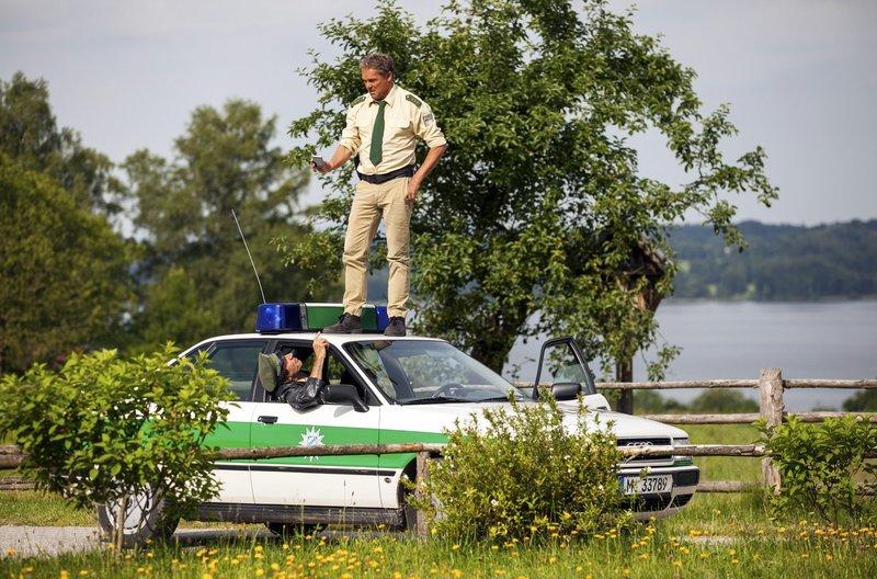 Hubert (Christian Tramitz, o. mit Helmfried von Lüttichau, u.) sucht auf dem Wagendach nach Handy-Empfang. – Bild: ARD/TMG/Chris Hirschhäuser