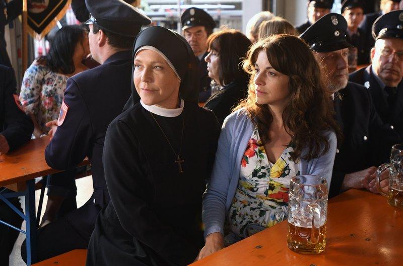 Schwester Hanna (Janina Hartwig, l) begleitet Franziska Obermaier (Bianca Hein, r.) zur Einweihungsfeier des neuen Löschzuges der Feuerwehr. Sie sind gespannt, ob Andreas kommt. – Bild: ARD/Barbara Bauriedl
