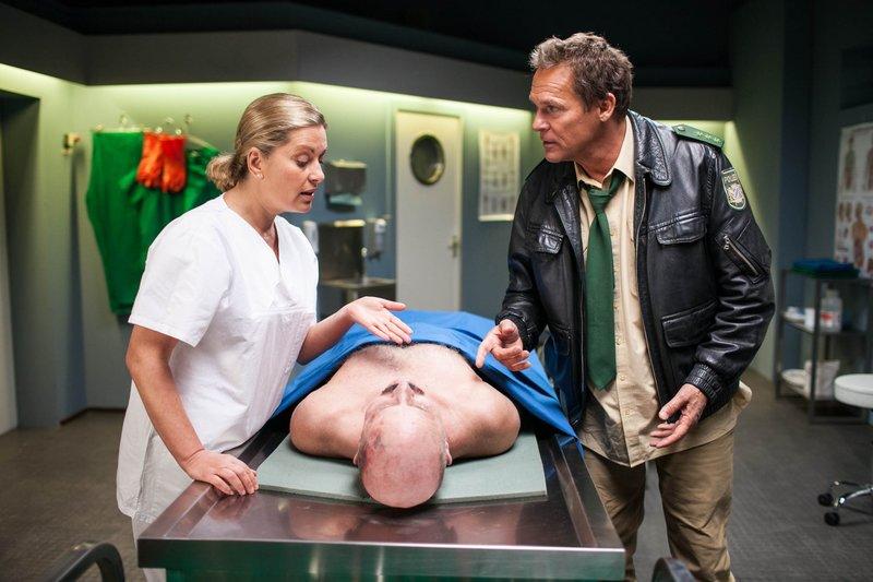 Hubert (Christian Tramitz) kann kaum glauben, was ihm Dr. Anja Licht (Karin Thaler) über den toten Polizisten zu berichten hat. – Bild: TMG