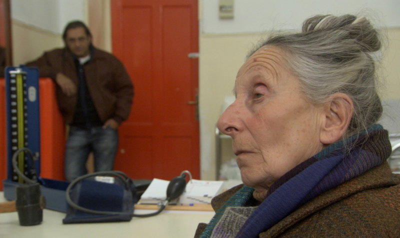 Stavros (Antonis Kafetzopoulos, im Hintergrund) macht sich große Sorgen um seine Mutter (Titika Saringouli), die ihn seit einem Schlaganfall immer wieder mit ausländischen Namen anspricht. – Bild: ZDF und Elissavet Moraki