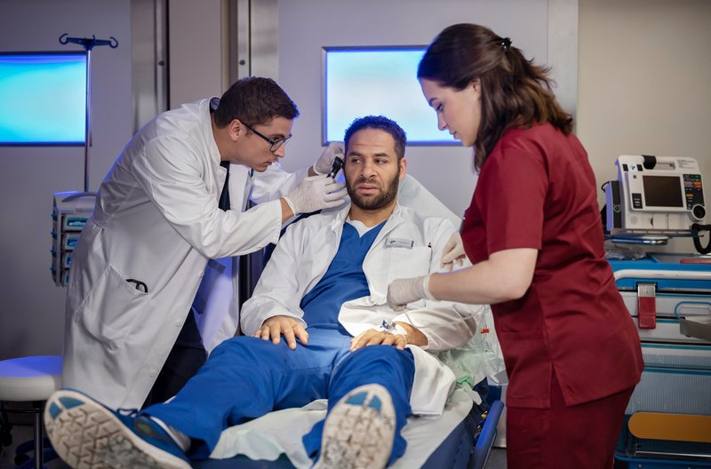 Dr. Moreau (Mike Adler, M.) sieht ein, dass er Hilfe braucht und lässt sich von Dr. Elias Bähr (Stefan Ruppe, l.) untersuchen. Jasmin (Leslie-Vanessa Lill, r.) assistiert. – Bild: ARD/Felix Abraham