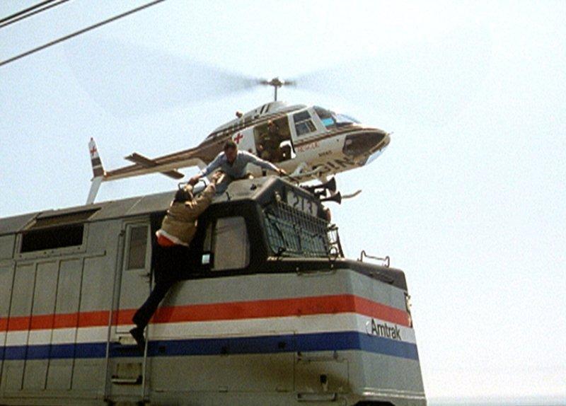 In einer spektakulären Aktion hilft Stuart Peters (William Shatner, oben) Jim Waterman (Paul L. Smith, l.) aus dem fahrenden Zug… – Bild: American Broadcasting Company