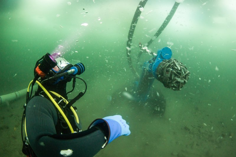 Sub-dredge nozzle and diver underwater. – Bild: Discovery Communications