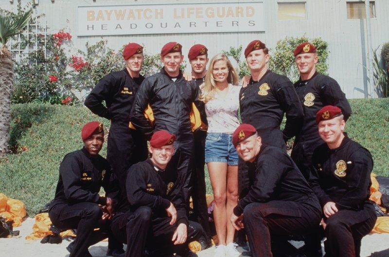 Jessie (Brooke Burns) posiert als Maskottchen in der Fallschirmspringer-Staffel, die direkt vor der Baywatch-Zentrale ihre Kunststücke probieren. – Bild: Nitro.