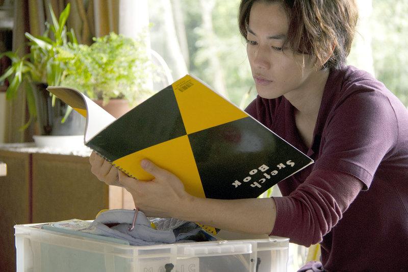 Koichi (Takeru Sato) sucht in den Unterlagen seiner Freundin nach der ersten Skizze eines Plesiosauriers, die sie jemals gezeichnet hat. Sie soll Atsumi ihr Selbstvertrauen wiederbringen. – Bild: ARTE France / © Condor Entertainment