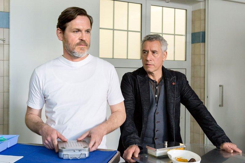 Dr. Blum (Ralph Herforth, r.) erfährt von Dr. Gregersen (Tobias Hoesl, l.), dass dieser unter Parkinson leidet. Dr. Blum bewundert den Arzt für seinen souveränen Umgang mit der Krankheit. – Bild: ARD/Steffen Junghans