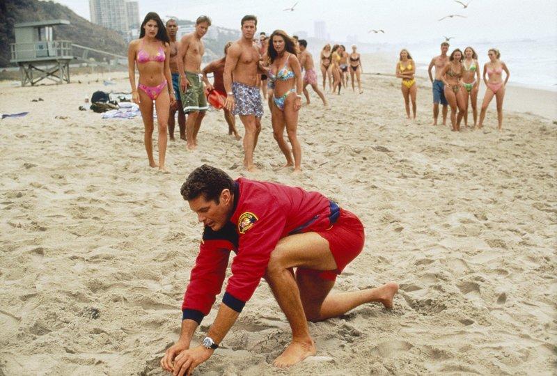 Mitch (David Hasselhoff) sucht im Sand nach weiteren, an den Strand gespülten Handgranaten. – Bild: Nitro.