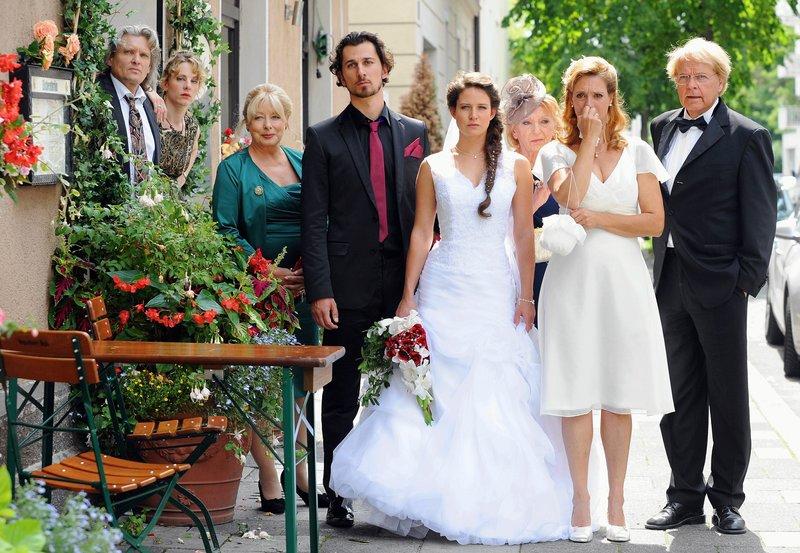 Die beiden Bräute Angelika (Gloria Nefzger, 4.v.l.) und Barbara (Carin C.Tietze, 2.v.l.), sowie die Hochzeitsgesellschaft sind entsetzt als klar wird, wer für die Bombendrohung verantwortlich ist (mit E. Fischer-Laughlin, 3.v.l., Daron Yates, 4.v.l., Ernst Hannawald, l., Julia Eder 2.v.l., Peter Fricke, r. und Peter Fricke, r.). – Bild: ARD