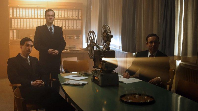 v.l.n.r. Karl Albrecht (Christoph Bach), Rottmann (Christoph Bertram), Theo Albrecht (Arndt Klawitter) schauen sich einen Werbefilm über SB-Läden an. – Bild: WDR/Kai Schulz