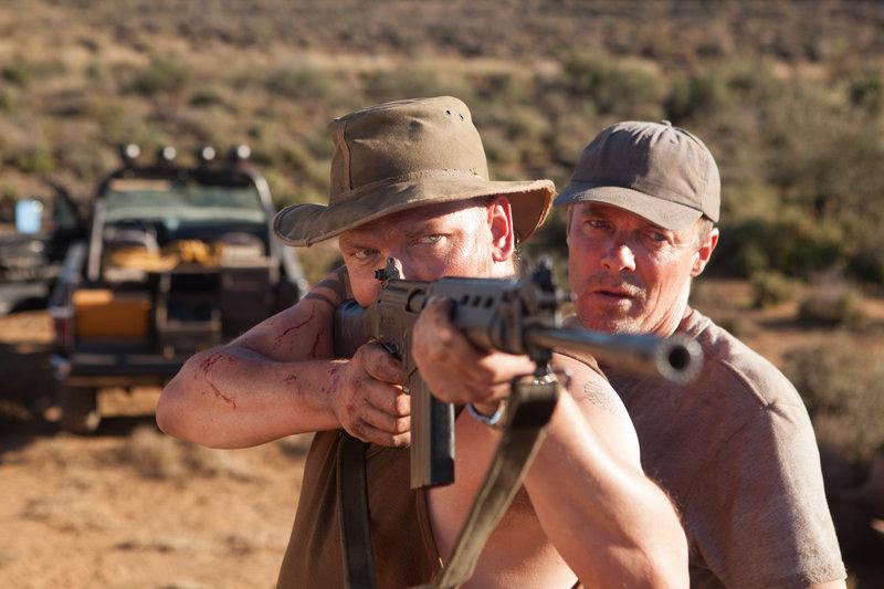Foy (Calvin Hayward, l.) und Bodley (Warrick Grier, r.) arbeiten für einen skrupellosen Waffenhändler. – Bild: ZDF und Ben Nott