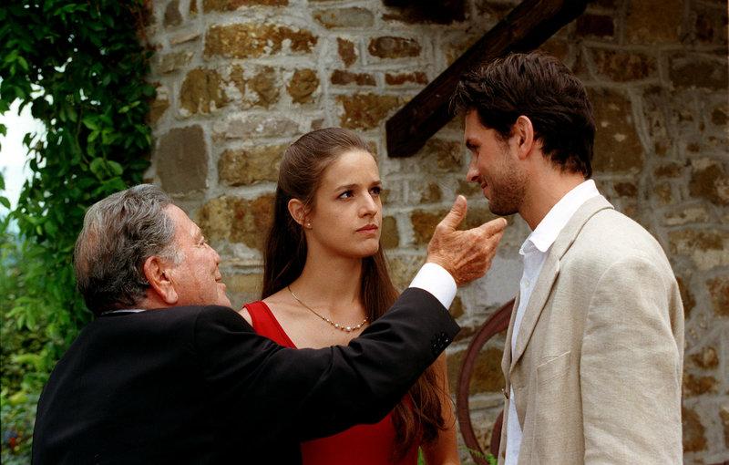 """""""Vino Santo - Es lebe die Liebe, es lebe der Wein"""", Gioia Altenburger soll als Steuerberaterin in die Kanzlei ihres Vaters Georg eintreten und den Sohn des Notars Dr. Winkler heiraten. Doch Gioia verliebt sich in einen Fremden namens Max und verbringt eine Nacht mit ihm. Als sie aber vor der Entscheidung steht, mit ihm gemeinsam Wien zu verlassen, ist sie zu feige - die Pflicht geht vor. Gioias Mutter Serafina, die seit Jahren getrennt von Georg im fernen Italien lebt, betreibt dort das familiäre Weingut. Weil Nonno, der Großvater Gioias, zu seinem 80. Geburtstag noch einmal ein großes Familienfest feiern möchte, fährt die Familie nach Italien. Dort trifft Gioia ihren Max wieder.Im Bild (v.li.): Raf Vallone, Helen Zellweger, Simon Verhoeven. – Bild: BR Fernsehen"""