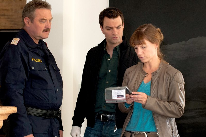 """""""Soko Kitzbühel"""", """"Vergeltung - Teil 1."""" Eine junge Frau liegt tot auf ihrem Bett. Was zunächst aussieht wie ein missglücktes Liebesspiel stellt sich als perfider Mord heraus. Die Tote ist PR-Expertin Eva Winger, die für die alteingesessene Tiroler Firma Traubach gearbeitet hat. Ihr Bruder Thomas ist bei der Polizei kein Unbekannter. Erst vor kurzem hat er eine Haftstrafe abgebüßt. Natürlich interessieren sich Karin und Lukas sofort für ihn. Aber nicht nur sie, sondern auch Chefinspektor Felix Stadler vom LKA Innsbruck. Porträts der Toten führen zum Kunstfotografen Paul Corelli. Karin findet heraus, dass er vor Jahren mit ähnlich gelagerten Frauenmorden in Verbindung gebracht wurde. Währenddessen stößt Lukas auf ein dunkles Geheimnis in der Familienchronik der Traubachs. Da werden Karin und Lukas zum Haus der Toten gerufen in das eingebrochen wurde. Die Jagd nach dem Verdächtigen verändert das Leben der Ermittler radikal.Im Bild (v.li.): Ferry Öllinger (Kroisleitner), Jakob Seeböck (Lukas Roither), Kristina Sprenger (Karin Kofler). – Bild: ORF III"""