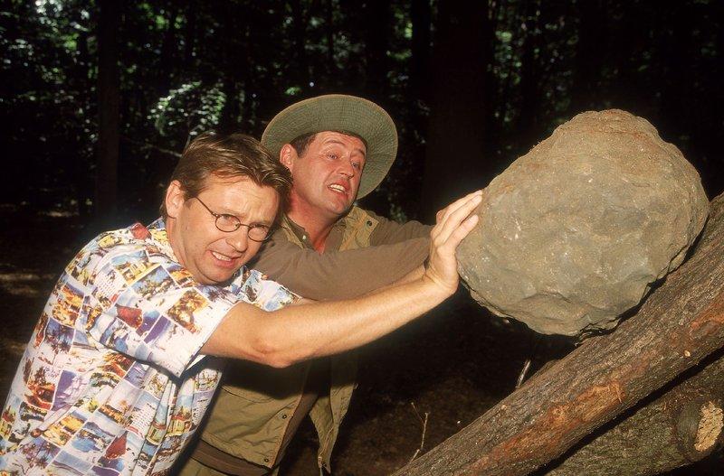 Um ein Gegengewicht für die Tierfalle zu haben, müssen Benno (Willi Thomczyk, r.) und Lothar (Rene Heinersdorff) einen schweren Stein auf den Baum schaffen. – Bild: TVNOW / Frank Dicks