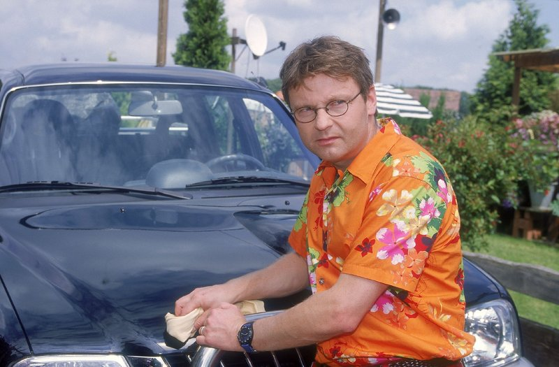 Lothar (Rene Heinersdorff) poliert gerade seinen niegelnagelneuen Geländewagen, als Benno mit einem alten Trecker auftaucht. – Bild: TVNOW / Frank Dicks