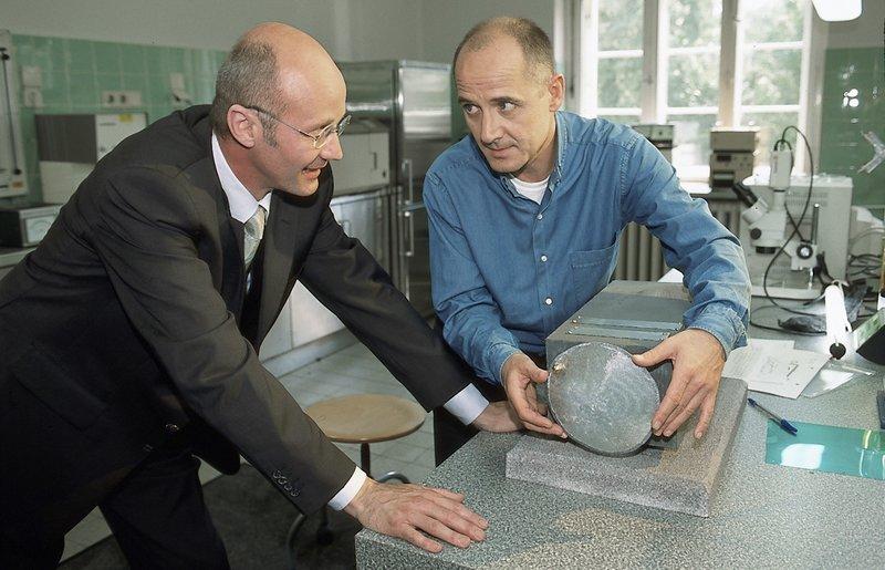 Gemeinsam bewundern Dr. Rainer Gottschalk (Chrisoph Wackernagel, l.) und Dr. Robert Kolmaar (Ulrich Mühe, r.) die Neutronenkanone von Ron Fugmann. – Bild: Katrin Knoke