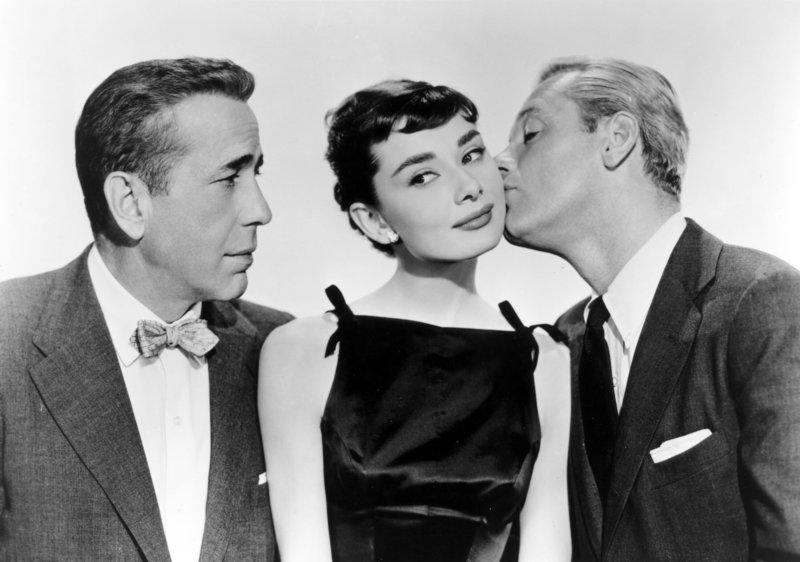 Zwischen zwei Männern: Sabrina (Audrey Hepburn) scheint es zu gefallen, dass Junggeselle Linus (Humphrey Bogart) skeptisch ihre Beziehung zu seinem Bruder und Playboy David (William Holden) betrachtet. – Bild: ORF