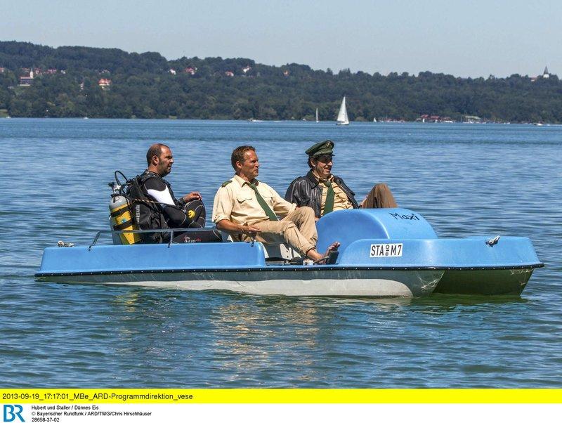 Hubert (Christian Tramitz, Mitte) und Staller (Helmfried von Lüttichau, rechts) sitzen in einem Tretboot und fahren auf den See hinaus. Yazid (Hannes Ringelstetter) sitzt hinter ihnen in Tauchermontur. Er soll für Hubert und Staller testen, ob man mit einem Schlittschuh unter Wasser an einer Boje hängen bleiben kann. – Bild: ARD/ARD/TMG/Chris Hirschhäuser