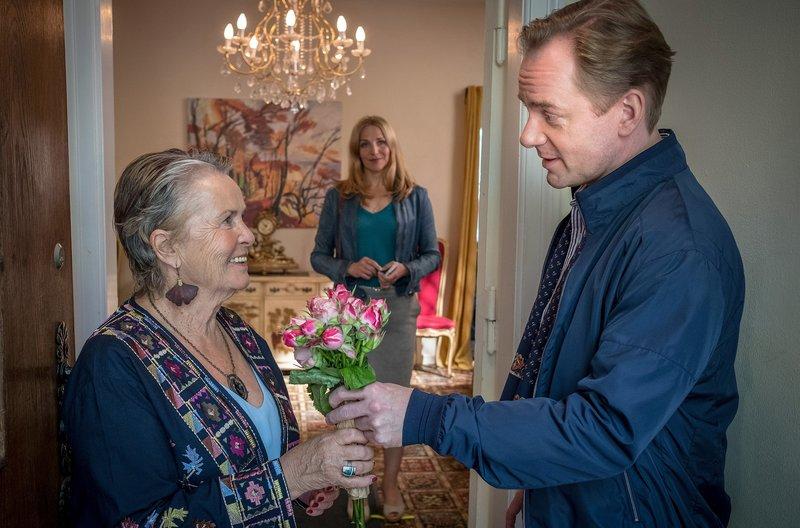 Nora (Tanja Wedhorn, Mitte) staunt: Dr. Heckmann (Patrick Heyn) bringt Roswitha Wing (Petra Kelling) Blumen mit. – Bild: ARD Degeto/Boris Laewen
