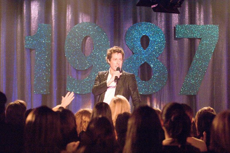 """Seit der Trennung von """"Pop!"""", Anfang der Neunziger, schlägt Alex Fletcher (Hugh Grant) sich mit 80er-Retroshows in Vergnügungsparks und auf Jahrmärkten durch, wo er die verstaubten Hits der Band in Karaoke-Qualität vor einer hysterischen Menge von Mittvierzigerinnen zum Besten gibt. Eines Tages erhält er die Chance auf ein Comeback ... – Bild: Puls 4"""