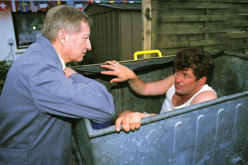 Pröter (Wilfried Herbst, l.) überrascht Benno (Willi Thomczyk) beim Suchen seines alten Trainingsanzugs in der Mülltonne. – Bild: TVNOW
