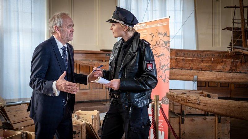 Prof. Munze (Heiner Hardt) ist außer sich. Der Ahnenschädel, das wichtigste Exponat seiner Ausstellung, wurde gestohlen. Melanie (Sanna Englund) nimmt die Einzelheiten auf. – Bild: ZDF und Boris Laewen (bola).