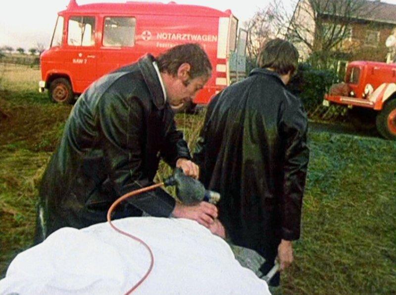 Der aus dem Brunnenschacht gerettete Peter (Rainer Basedow, liegend) wird zum Notarztwagen 7 getragen. – Bild: HR/hr media