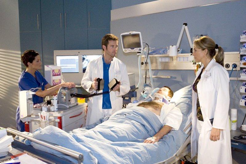 Oberarzt Dr. Stefan Jung (Jan Hartmann, l.) und Dr. Shirley Wilson (Caroline Beil, r.) sind in größter Sorge: der Patient Herr Schiller hat einen Herzstillstand. Schwester Karen Wagner (Yvonne Burbach, l.) muss hilflos zusehen. – Bild: ORF 2