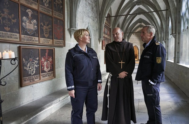 Paul Schott (Tim Wilde, r.) und Nele Fehrenbach (Floriane Daniel, l.) treffen Abt Barnabas (Ulrich Gebauer, M.) im Kreuzgang von Kloster Oberzell. – Bild: Das Erste