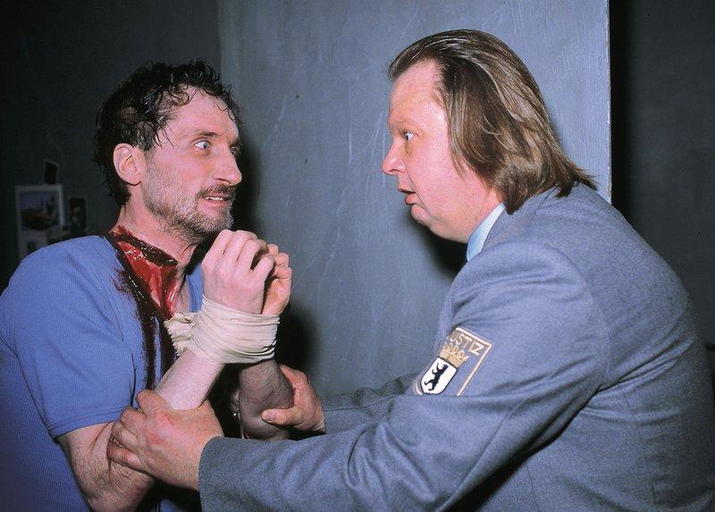 Der Wächter Roth (Andreas Ammann, r.) findet einen blutüberströmten Gefangenen (Komparse) in dessen Zelle. – Bild: RTLplus