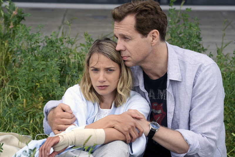 """""""Ein starkes Team – Vergiftet"""": Anja (Jytte-Merle Böhrnsen) und Immo Haferkamp (Thomas Heinze) sitzen nebeneinander an einem Fluss im Gras. Er hat seinen Arm schützend um sie gelegt. – Bild: ZDF/Katrin Knoke"""